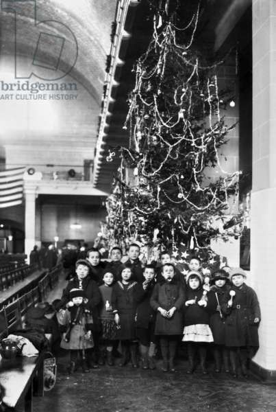 ELLIS ISLAND: CHRISTMAS, 1920 Group of immigrant children photographed in front of a Christmas tree inside the registry room at Ellis Island, New York City, 1920.