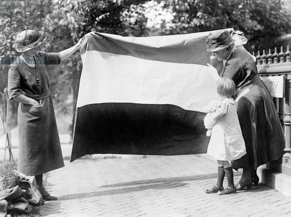 SUFFRAGETTES, c.1915 Two suffragettes show their banner to a young girl. Photograph, c.1915.