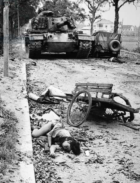 VIETNAM WAR: HUE, 1968 An American tank passes the bodies of dead Vietnamese civilians during the Battle of Hue, Febraury 1968.