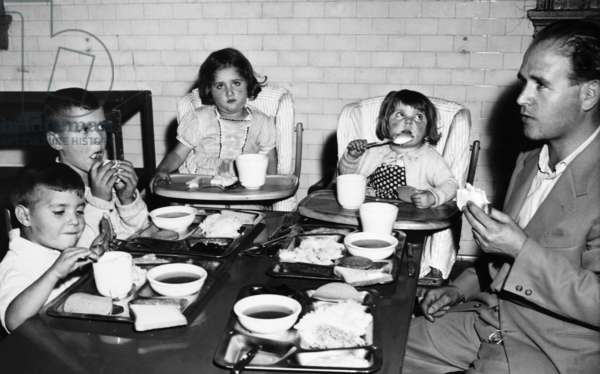 IMMIGRATION, 1950 An Italian family having a meal while being detained at Ellis Island. Photograph, 1950.