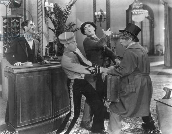 MARX BROTHERS, 1929. in 'Coconuts,' 1929. Groucho, behind the desk, watches as Harpo, in top hat, and Chico, wrestle with the bellhop.