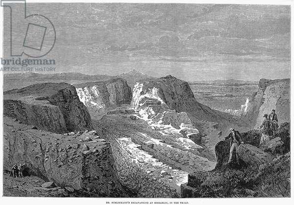 HEINRICH SCHLIEMANN (1822-1890). German traveller and archeologist. View of the excavation at Hissarlik, Turkey, site of ancient Troy. Wood engraving, English, 1877.