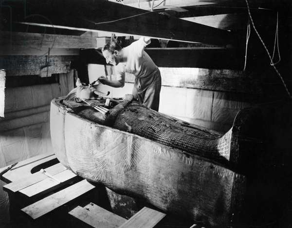 HOWARD CARTER (1873-1939) English archaeologist. Brushing dust off the nose of the second coffin in the sarcophagus of King Tutankhamen in the tomb in the Valley of the Kings, Egypt, October 1925. Photographed by Harry Burton.