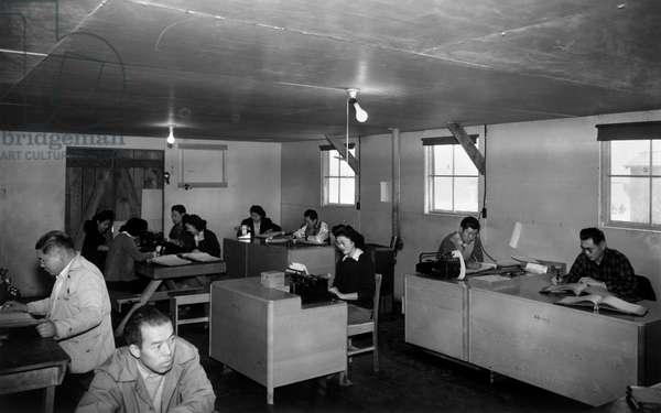 JAPANESE INTERNMENT, 1943 Men and women at work in an office at the Manzanar Relocation Center for Japanese-American at Owens Valley, California. Photograph by Ansel Adams, 1943.