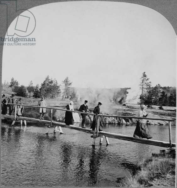 YELLOWSTONE: TOURISTS, c.1904 Tourists walking across a footbridge among the geysers in Yellowstone National Park, Wyoming. Stereograph, c.1904.