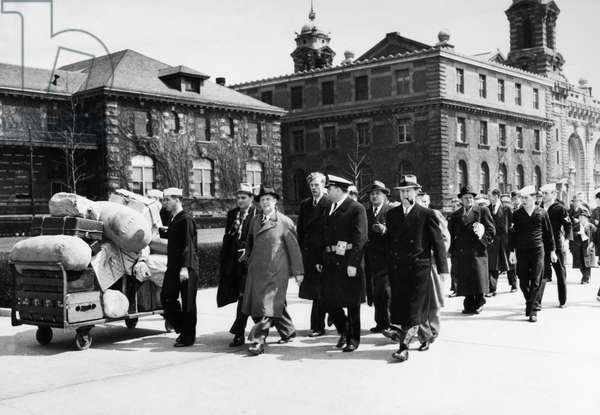 ELLIS ISLAND, 1941 Danish merchant marine seamen (in civilian clothing) from a ship in U.S. custody after the German invasion of Denmark in World War II, arriving at their new quarters on Ellis Island assisted by United States Coast Guardsmen, 31 March 1941.