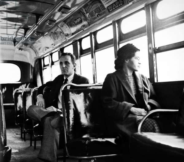 ROSA PARKS (1913-2005) American civil rights advocate. Parks sits at the front of a public bus (formerly 'whites only') in Montgomery, Alabama, 21 December 1956, the day buses were integrated in the city. Seated behind her is reporter Nicholas C. Criss.