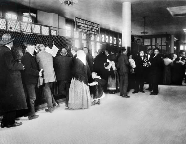 ELLIS ISLAND: IMMIGRANTS Immigrants purchasing train tickets at the railroad ticket office at Ellis Island, New York City. Photograph, late 19th or early 20th century.