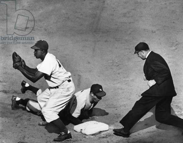 WORLD SERIES, 1947 Jackie Robinson of the Brooklyn Dodgers makes a catch as Joe DiMaggio of the New York Yankees dives back into first base, during a game of the 1947 World Series at Ebbets Field, Brooklyn, New York. Photograph.