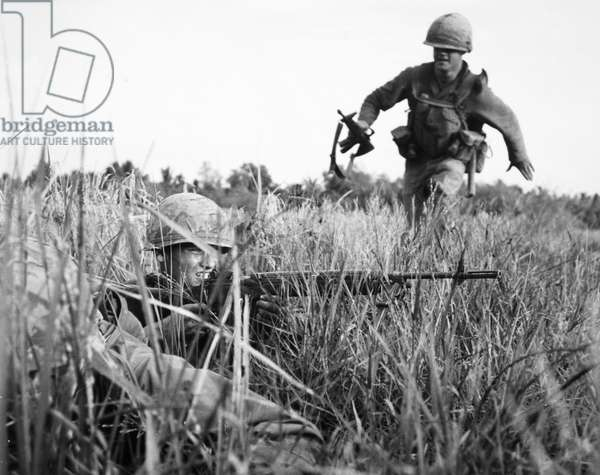 VIETNAM WAR: RICE PADDY A U.S. infantryman runs through a rice paddy in South Vietnam covered from snipers by a fellow soldier, January 1967.