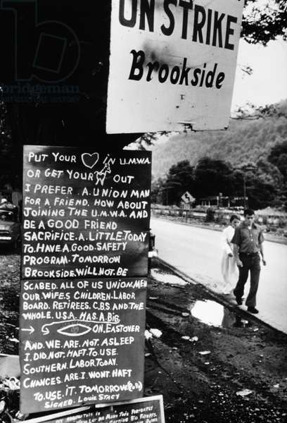 KENTUCKY: MINE STRIKE, 1974 A boy and girl walk past a sign for the United Mine Workers, on strike against the Brookside mine in Harlan, Kentucky. Photograph by Jack Corn, 1974.