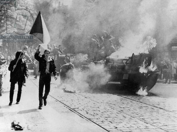 CZECH PROTEST, 1968 Defiant young Czechs carrying their country's flag past a burning Soviet tank on a street in Prague, in protest of the Soviet-led Warsaw Pact invasion of Czechoslovakia, 21 August 1968.