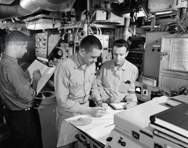 NAVY: USS NAUTILUS, 1958 Sailors onboard the USS Nautilus, checking position of the ship during the final approach to the North Pole. Photograph, 1958.