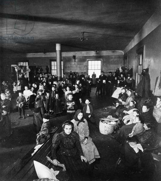 ELLIS ISLAND, c.1907 Women and children, immigrants from Europe, in a waiting room at the immigration station in New York Harbor, c.1907.