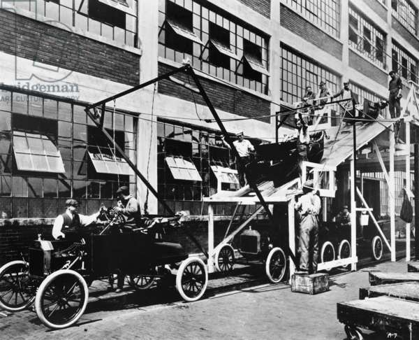 FORD ASSEMBLY LINE, 1913 The last stage of the Model T assembly line at the Ford automobile plant in Highland Park, Michigan. Photograph, 1913.