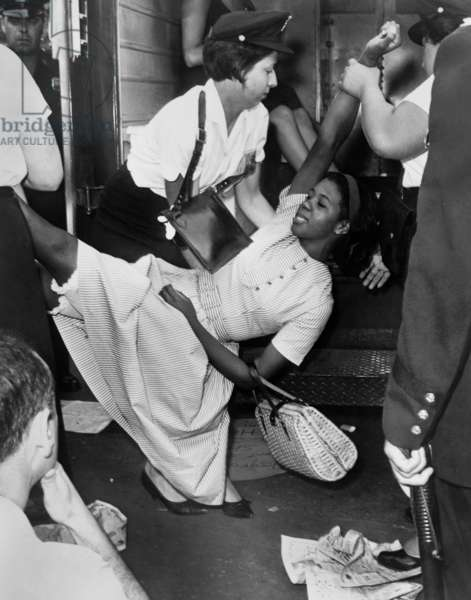NEW YORK: CIVIL RIGHTS African American woman being carried to a police wagon during a Civil Rights demonstration in Brooklyn, New York. Photographed by Dick DeMarsico, 1963.