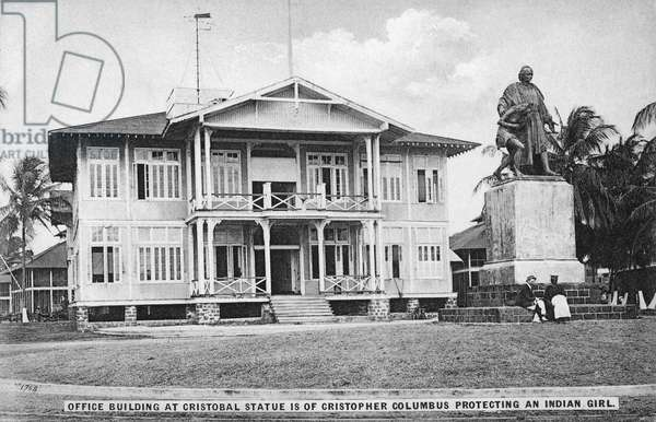 PANAMA: OFFICE, c.1910 Office building in Panama City, with a statue of Christopher Columbus protecting a Native American. Photo postcard, c.1910.