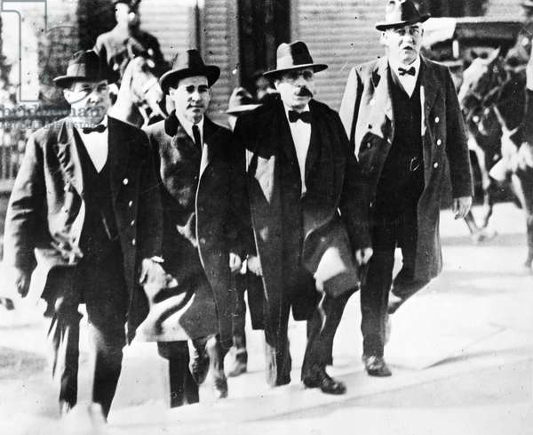 SACCO AND VANZETTI, 1921 Flanked by Massachusetts deputy sheriffs, Nicola Sacco (second from left) and Bartolomeo Vannzetti enter the Norfolk County courthouse at Dedham, Massachusetts, 1921.