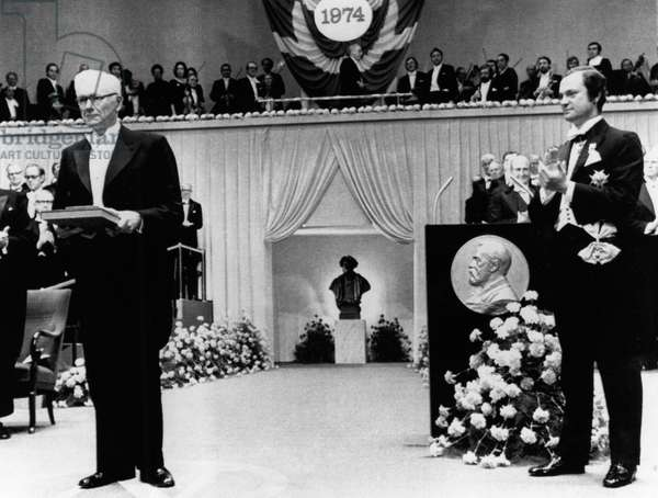 PAUL J. FLORY (1910-1985) American chemist. Photographed after being presented with the Nobel Prize in Chemistry by King Carl XVI Gustaf of Sweden (who applauds at right), during ceremonies in Stockholm, 10 December 1974.
