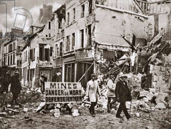 WORLD WAR I: CLEMENCEAU French Prime Minister Georges Clemenceau walking through the streets of Noyon despite the threat of land mines, France. Photograph, c.1916.
