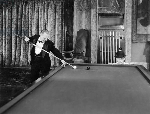 WILLIE HOPPE (1887-1959) American billiard player. Performing a stunt with actor Buster Keaton. Photograph, c.1930.