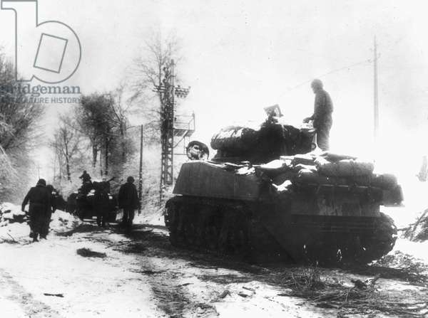 WWII: BATTLE OF THE BULGE Tanks and infantrymen of the 82nd Airborne Division push through the snow in Belgium: December, 1944.