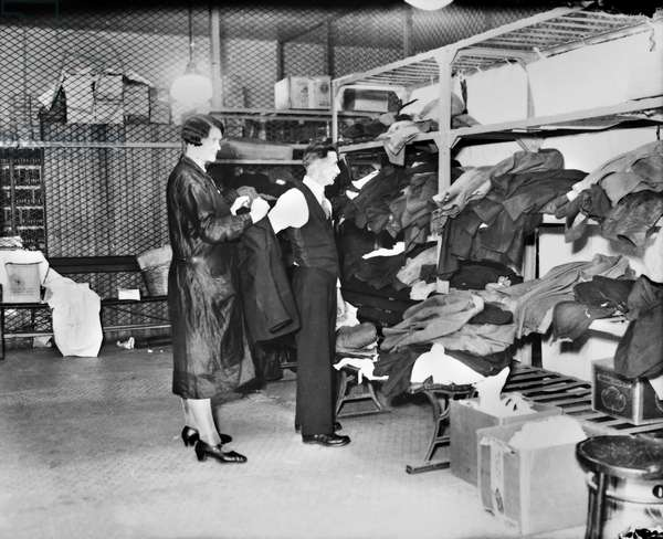 ELLIS ISLAND: CLOTHING ROOM A woman helping an immigrant man put on a jacket in the clothing room at Ellis Island, New York City. Photograph, 1931.