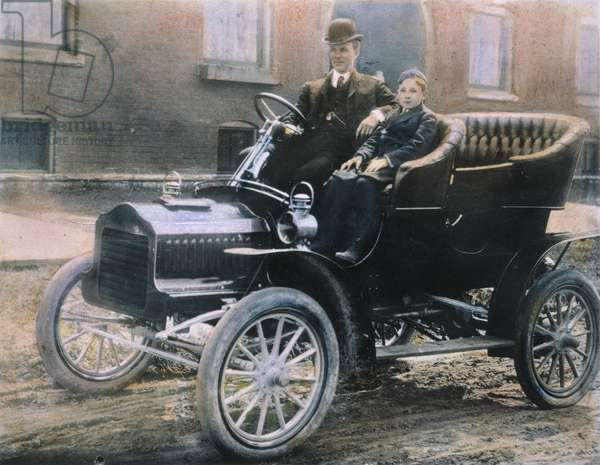 HENRY FORD (1863-1947) and his son, Edsel, in a 1905 Model F Ford in front of their home on Hendrie Avenue, Detroit.