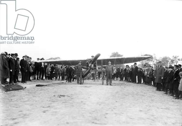 LOUIS BLERIOT (1872-1936) French engineer and pioneer aviator. Bleriot in his monoplane, his mechiniacs in front, and French onlookers, n.d.