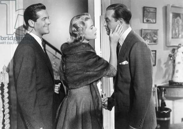 GRACE KELLY (1928-1982) American actress and Princess of Monaco, 1956-1982. In 'Dial M For Murder,' 1954, about to kiss Ray Milland with Robert Cummings behind her.