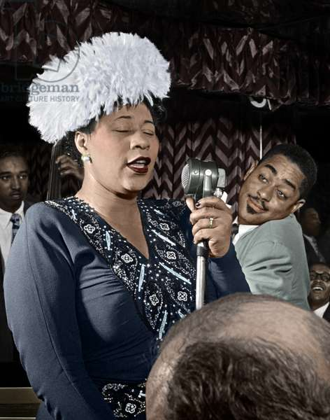 ELLA FITZGERALD (1917-1996) American singer. Performing on stage with Dizzy Gillespie. Photograph by William P. Gottlieb, c.1947.