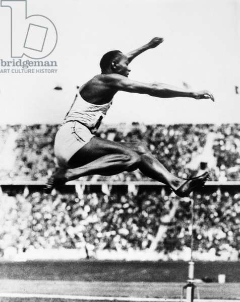 JESSE OWENS (1913-1980) American athlete. Owens in the midst of his broad jump leap, which was responsible for one of the four gold medals he won and three track and field records he set at the 1936 Berlin Olympic Games.