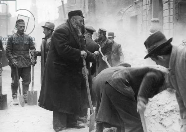 WARSAW GHETTO UPRISING An old man is forced to clear rubble after the uprising in the Warsaw Ghetto in 1943.