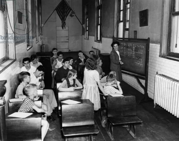 ELLIS ISLAND, 1947 Children attending a class taught by social worker Jennie Pratt, while being detained at Ellis Island. Photograph, 1947.