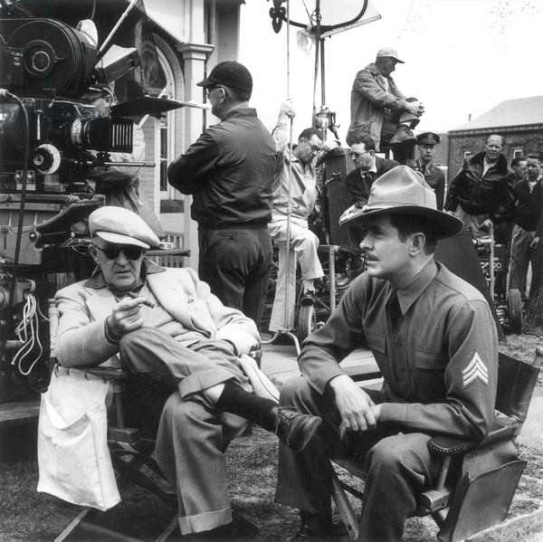 "JOHN FORD (1895-1973) American motion-picture director. Ford (seated, left) with Tyrone Power on the set of ""The Long Gray Line,"" 1954."