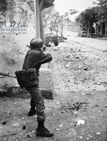 VIETNAM WAR: TET OFFENSIVE A South Vietnamese soldier fires his automatic weapon in a street in Hue during the Viet Cong Tet Offensive, February 1968.