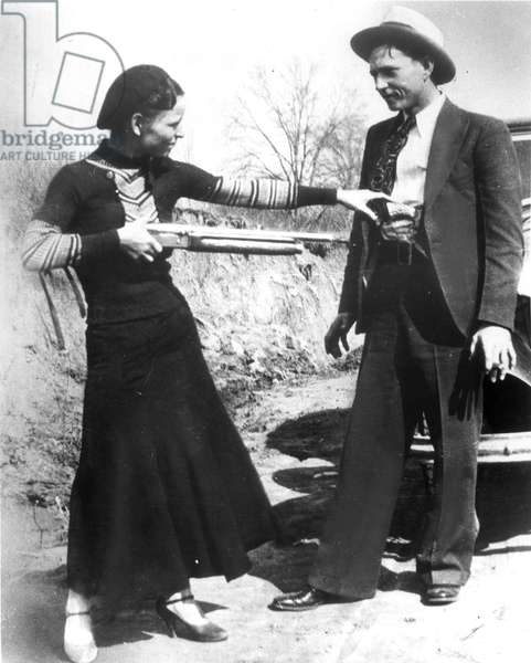 BONNIE AND CLYDE, 1933 American criminal Bonnie Parker (1911-1934) playing at holding up her partner, Clyde Barrow (1909-1934). Photographed in 1933.