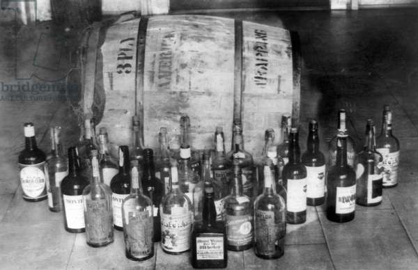 CONFISCATED WHISKEY, 1920s Bottles and keg of whiskey confiscated during Prohibition in America, 1920s.