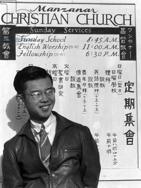 JAPANESE INTERNMENT, 1943 Portrait of a man, Tatsuo Miyake, in front of a sign for the Manzanar Christian Church at the Manzanar Relocation Center for Japanese Americans, near Owens Valley, California. Photograph by Ansel Adams, 1943.