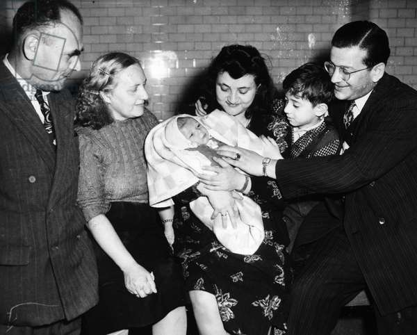 JEWISH REFUGEES, 1949 Mr. and Mrs. Abraham Miller, left, who live in the United States, greeting their daughter, son-in-law, and grandchildren at Ellis Island. The younger couple is on their way to Israel from Shanghai, China, where they spent the war years as refugees from Europe. Photograph, 1949.