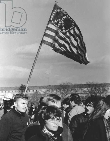 ANTI-WAR PROTEST, 1969 Protesters waving an American flag with a peace sign demonstrate on the Mall in Washington, D.C., on 15 November 1969, against the war in Vietnam.