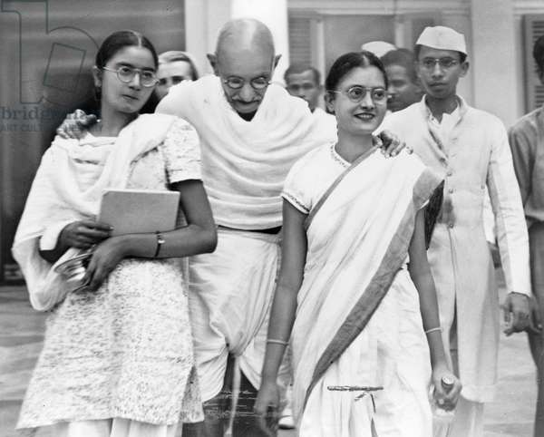 MOHANDAS GANDHI (1869-1948) Hindu nationalist and spiritual leader. Photographed with his granddaughters in New Delhi, India, 1947.
