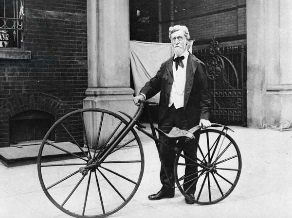 VELOCIPEDE, 1914 George C. Maynard, curator of technology at the United States National Museum, posing with an old velocipede, or 'boneshaker,' outside the east entrance of the Arts and Industries Building at the Smithsonian Institution in Washington, D.C. Photographed in 1914.