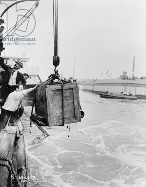 HARRY HOUDINI (1874-1926) American magician. A crate containing Houdini being lowered into New York Harbor. Photograph by Carl Dietz, c.1914.