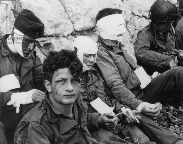 WORLD WAR II: D-DAY, 1944 Wounded American assault troops resting at Omaha Beach following the 6 June 1944 invasion of Normandy, France.