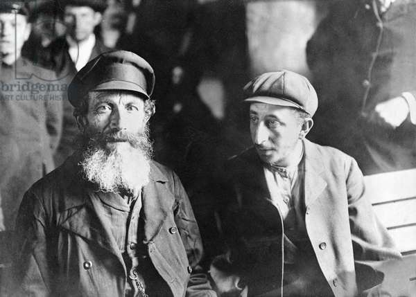 NEW YORK: IMMIGRANTS A European immigrant and his son, sitting on a bench after their arrival in New York City. Photograph, early 20th century.