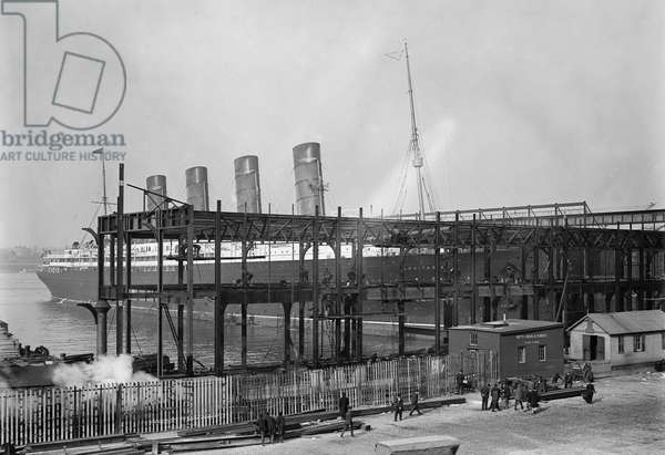 NEW YORK: LUSITANIA, 1908 The Cunard steamship 'Lusitania' docking at the Hudson River piers with construction of new piers in foreground, 20 November 1908.