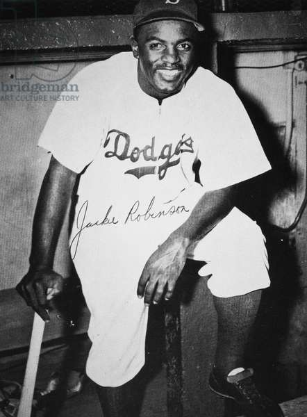 JACKIE ROBINSON (1919-1972) John Roosevelt Robinson, known as Jackie. American baseball player. Photograph of Robinson as a member of the Brooklyn Dodgers, c.1950, with autograph signature.