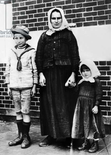 ELLIS ISLAND: IMMIGRANTS A Czechoslovakian woman with two children. Photographed at Ellis Island, 1920.