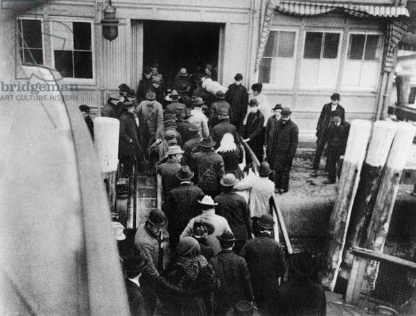 NEW YORK: BATTERY, 1902 Immigrants disembarking from the ferry boat from Ellis Island to the Battery in Lower Manhattan. Photograph, 1902.